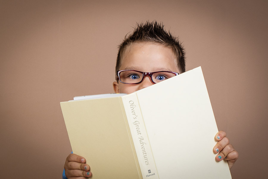 a close up of a boy peeking his eyes over a book