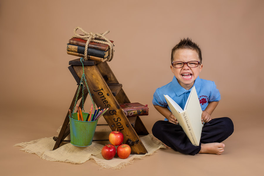 a boy laughing reading a book