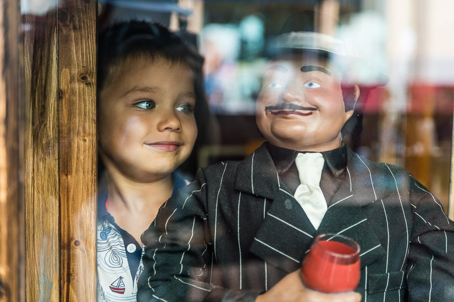 a boy behind a window, looking at a minature model of Giovanni Malacrino, Cardiff