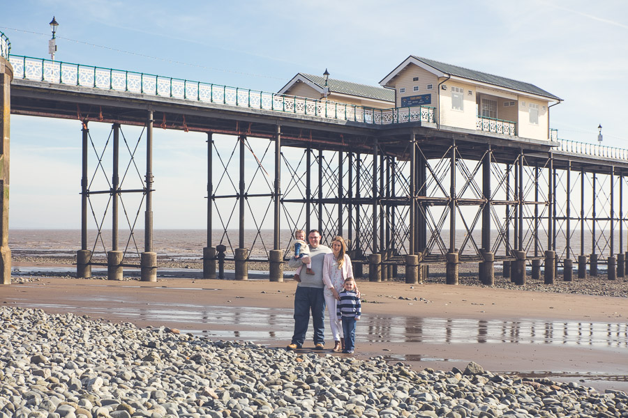 a family of four on a beach with a pier behind them