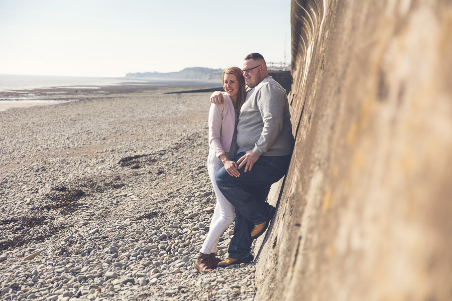 a couple stood leaning against a wall on a beach