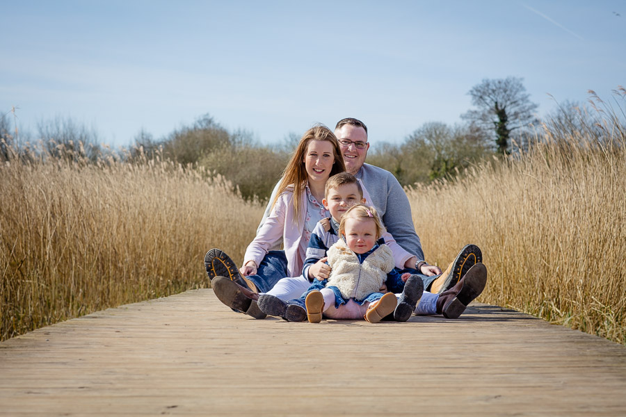 a family of four sat down on a board walk